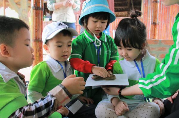 Các bạn nhỏ chăm chú in tranh Đông Hồ dưới sự hướng dẫn nhiệt tình của các nghệ nhân.