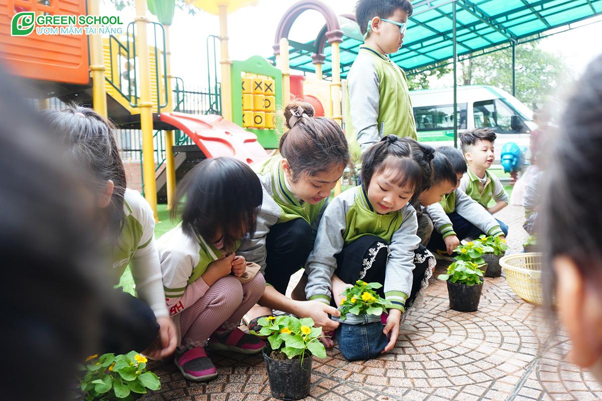 Hình ảnh bé tham gia vào giáo dục xanh, trồng cây vào túi tài chế